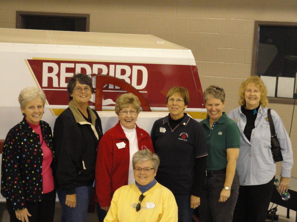 Visiting the Indian Hills Community College Aviation hangar (L-R: Jane Berg, Carol Berg, Deb McGee, Celma Higgins, Jeneanne Visser, Elaine Fitch; Minnetta Gardinier (kneeling))